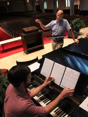 Singer Michael McCown, top, and accompanist Marc Sanders discuss how a song will be performed when they present an Aug. 31 concert at First Baptist Church. McCown is on vacation from Frankfurt, Germany, where he sings with Oper Frankfurt.