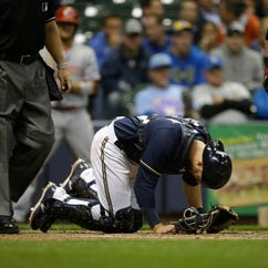 Milwaukee Brewers catcher Jonathan Lucroy bends over after taking a foul tip off his toe during the sixth inning of a baseball game  against the Cincinnati Reds Monday, April 20, 2015, in Milwaukee. Lucroy left the game and the Brewers announced after the game that Lucroy will be placed on the DL with a broken left toe. (AP Photo/Jeffrey Phelps)  ORG XMIT: WIJP119