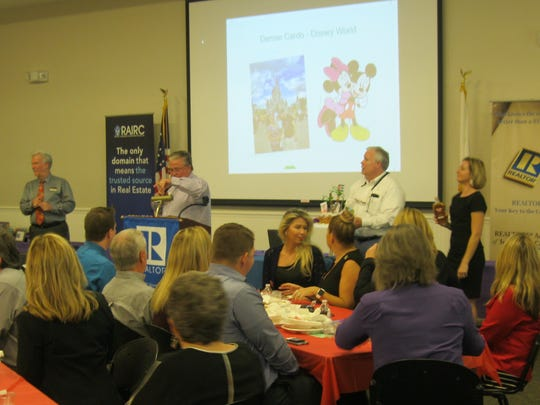 Auctioneer Wesley Davis, center, encourages members of the REALTORS Association of Indian River County to bid on a cake.