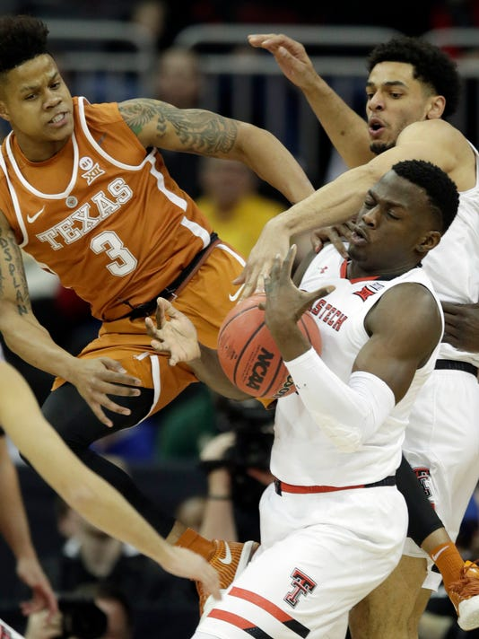 Texas Tech center Norense Odiase, center, rebounds against Texas guard Jacob Young, left, and teammate Zach Smith, right, during the first half of an NCAA college basketball game in quarterfinals of the Big 12 men's tournament in Kansas City, Mo., Thursday, March 8, 2018. (AP Photo/Orlin Wagner)
