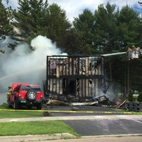 Fire crews work to put out a fire at 82 Overlake Drive in Milton on Tuesday.
