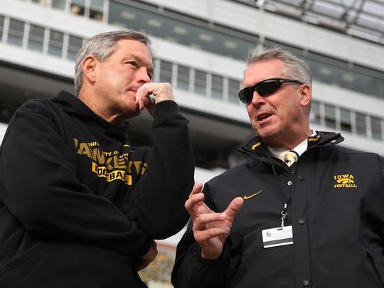 Iowa head football coach Kirk Ferentz, left, and athletic director Gary Barta talk before a 2013 game against Northwestern.