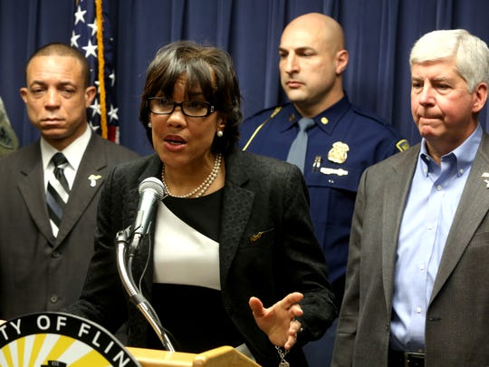 Mayor of Flint Karen Weaver talks to the media during a press conference as Michigan Governor Rick Snyder (far right) listens to her inside a room at the City of Flint Municipal Center in Flint, Michigan on Wednesday, Jan.  27, 2016.