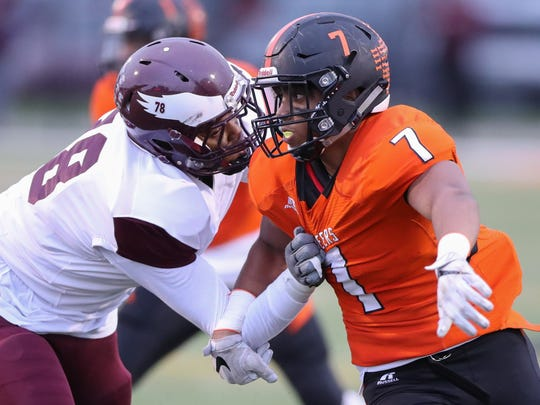 Romulus' Quinton Barrow blocks Dearborn's Ali Fayad during Dearborn's 22-8 win over Romulus Friday in Dearborn.