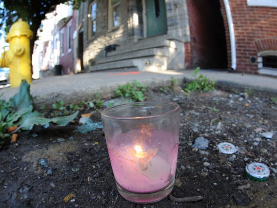A lit candle sits near where Patrick Fabien Winter, 17, was shot and killed on June 14, 2014. Leonard Green III, now 17, pleaded guilty on Wednesday to third-degree murder and related offenses in his death.
