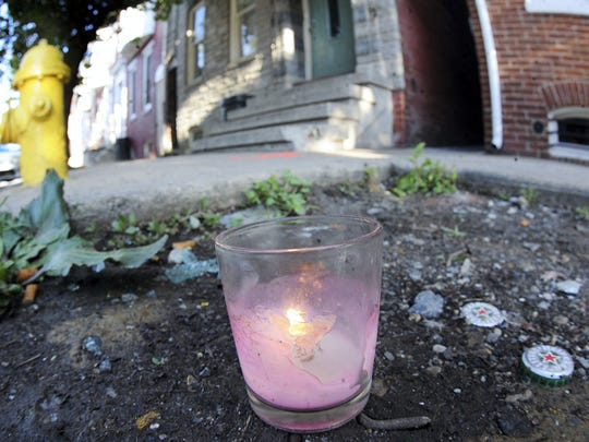 A lit candle sits near where 17-year-old Patrick Winter was shot and killed on Saturday, June 14, 2014.