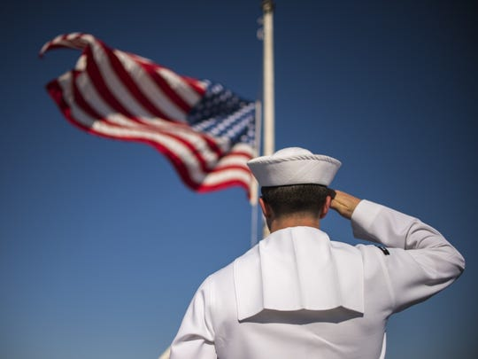 Operations Specialist 3rd Class Benjamin Kirkpatrick, assigned to the aircraft carrier USS Carl Vinson (CVN 70) color guard, salutes the national ensign as it flies at half-mast in honor of the seven Sailors who perished aboard the guided-missile destroyer USS Fitzgerald (DDG 62) during a collision at sea. Carl Vinson is pierside at its homeport in San Diego, Calif., after completing a five-month deployment to the western Pacific. (U.S. Navy photo by Mass Communication Specialist 3rd Class Matthew Granito/Released)