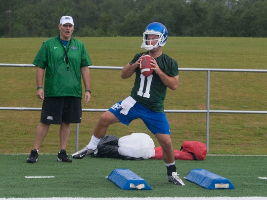 UWF football coach, Pete Shinnick, left, keeps an eye on quarterback, Kaleb Nobles, right, during team practice on Aug. 11, 2016.