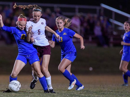 Caldwell's Hannah Young (17) and Henderson's Maddie Griggs (5) try to control the ball as Henderson County plays Caldwell County in the Girls 2nd Region final played at Madisonville North Hopkins High School in Hanson Thursday, October 19, 2017.