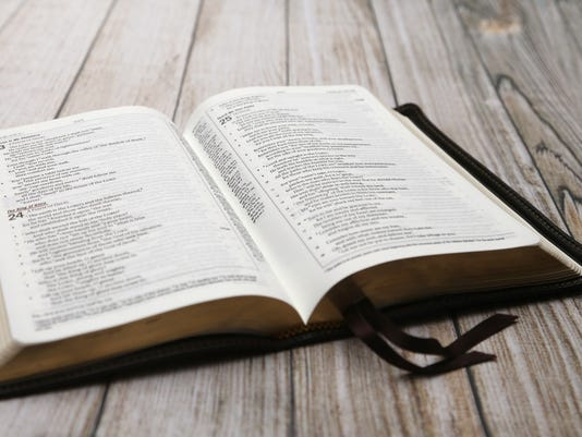An Opened Bible on a White Distressed Wooden Table