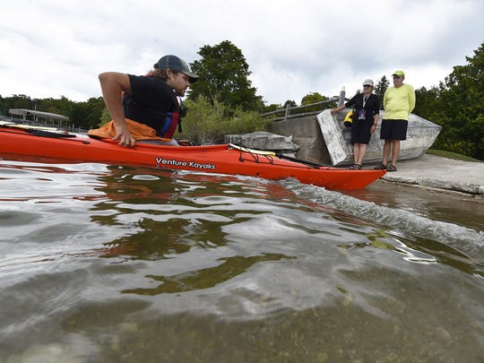 ACA certified Blaze Wilde of DC Adventure Center demonstrates a personal preference on how to disembark from a sit-in style kayak to advanced kayakers Dennis and Janet Johnson of Sister Bay at the Egg Harbor Beach.