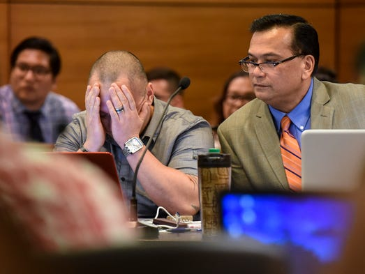 Defendant Mark Torre Jr., left, covers his face with