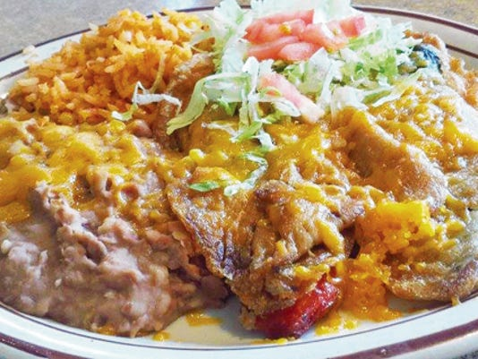 The Chile Relleno Plate (9.65) comes with two rellenos smothered in green chile, with a side of refried beans, rice and lettuce and tomato.