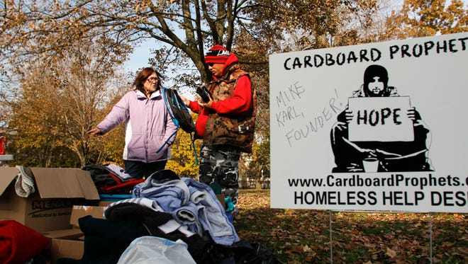 Cardboard Prophets volunteer Kitty Henry of Lansing chats with a Lansing area homeless man Tuesday, Nov. 14, 2017, at Reutter Park in downtown Lansing.  The organization set up tables with water and snacks, and brought boxes of winter wear, shoes, and boots for those in need.  They are stationed on the southwest corner of the park each Tuesday and Wednesday from 11 AM to 2 PM.