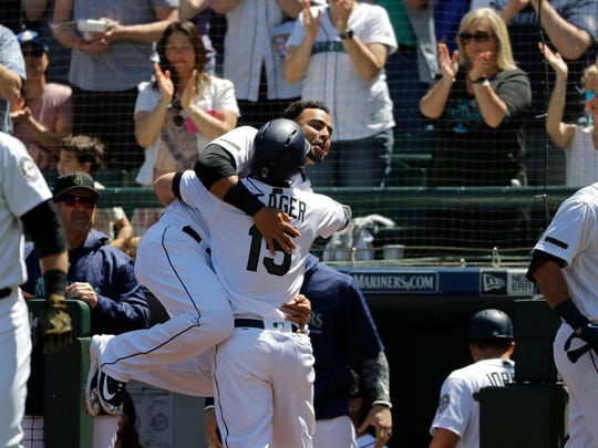 Fans cheer as Seattle Mariners' Kyle Seager (15) is hugged by Nelson Cruz after Seager hit a solo home run against the Minnesota Twins during the fourth inning of a baseball game, Sunday, May 27, 2018, in Seattle. (AP Photo/Ted S. Warren)