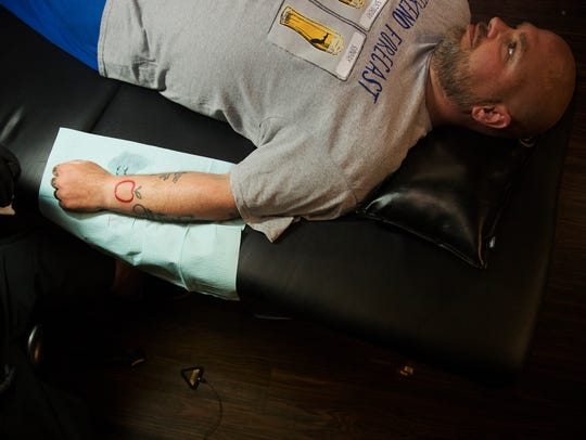 Ray Matthew gets a new tattoo on Sunday during a fundraising