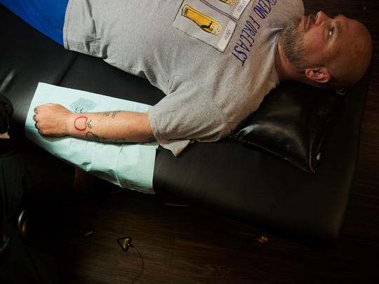 Ray Matthew gets a new tattoo on Sunday during a fundraising event for SalusCare at Altered Tattoo Company in south Fort Myers. Matthew's employer, Mr. GreensProduce, is donating $1,000 to SalusCare for each of up to 10 people who agree to have the company's logo— a red outline of an apple with a green leafy stem — tattooed on their body. SalusCare offers behavioral healthcare services in Southwest Florida.