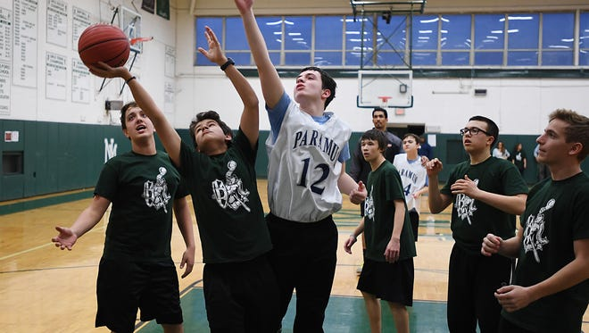New Milford High School hosts a basketball game through its Play Unified special needs program on Wednesday. From left, New Milford's Kyle Kollais looks on as his teammate, Sevastian Pinzon, battles for the ball with Paramus' Luke Farag.