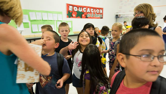 Jornada Elementary School second-grader Angelica Urquides, center, waves to the camera, Monday, August 15, 2016, on the first day of the school year.