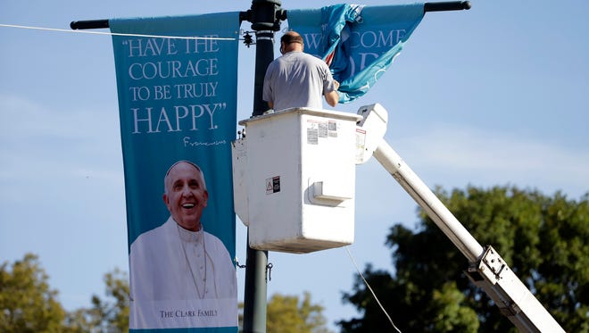 A worker hangs banners ahead of Pope Francis' scheduled visit, on the Benjamin Franklin Parkway in Philadelphia. After months of angst over long security lines and onerous travel, organizers still expect more than a million people for Pope Francisí outdoor Mass in Philadelphia. (AP Photo/Matt Rourke, File) ORG XMIT: NYSB702