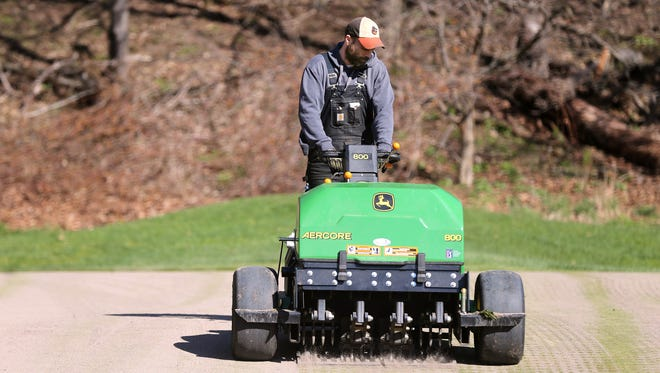 Dave Armstrong aerates the green on the 7th hole at Durand-Eastman Golf Course.