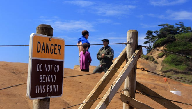 Lisa Stevenson, a park ranger with the Oregon Parks and Recreation Department, talks to a man and has daughter who walked through the fence at Cape Kiwanda State Natural Area.