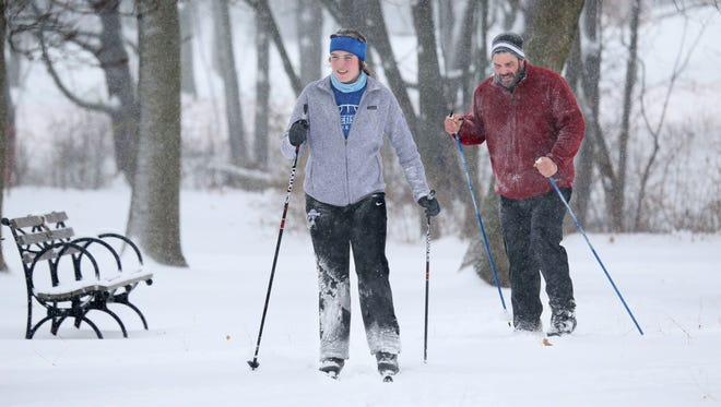 Maggie McGann (left) and her father Mike McGann, both of Whitefish Bay, went cross-country skiing through Lake Park in Milwaukee as snow continued to fall around them on Sunday, Dec. 11, 2016.