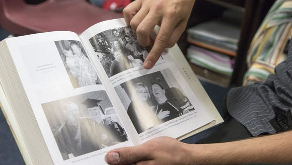 Tyler DeMoe points to photographs in a book that includes