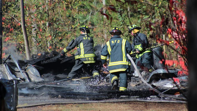 Firefighters work at the scene of a garage fire Wednesday near Mosinee.