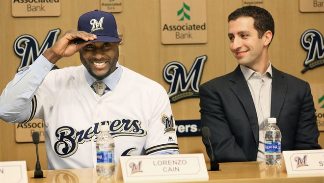 Lorenzo Cain shows off his new Brewers uniform as GM David Stearns looks on during a news conference Friday afternoon at Miller Park.