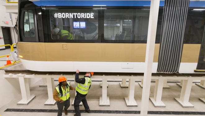 A Brookville Corp. employee (left) and a City of Milwaukee employee examine The Hop, the first of the new city streetcars  at the Streetcar Operations and Maintenance Facility at 450 N. 5th St. in Milwaukee.