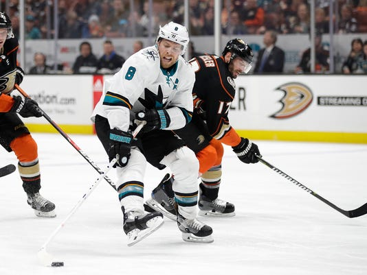 San Jose Sharks' Joe Pavelski, left, moves the puck away from Anaheim Ducks' Ryan Kesler during the second period of an NHL hockey game Sunday, Jan. 21, 2018, in Anaheim, Calif. (AP Photo/Jae C. Hong)
