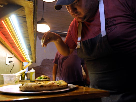 Owner Jason Adams puts the final touches on a pizza