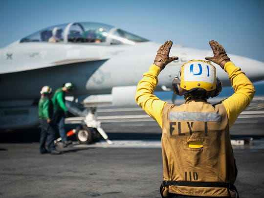 """Sailor Jessica Brown, from Bakersfield, Calif., directs a plane on the aircraft carrier USS Carl Vinson, currently deployed supporting strike operations in Iraq and Syria, a campaign formally named """"Operation Inherent Resolve."""""""