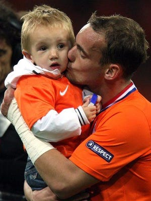 Netherlands' Wesley Sneijder kisses his baby, who probably smiles and cuddles a lot.