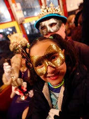"""Mia Weakley, 11, sits on the lap of her godfather, Chuck Rogers, inaugural King """"Societe des Champs Elysee,"""" as they ride the Rampart-St. Claude street car line, which just opened last fall, to commemorate the official start of Mardi Gras season, in New Orleans, Friday, Jan. 6, 2017. Wearing masks and festive costumes, they honored their king and queen and adults later reconnoitered at a neighborhood bar and danced as a brass band played """"Carnival Time,"""" after their red street car ride."""