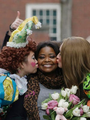 Guan-Yue Chen, Hasty Pudding Theatricals President, left, and Dan Milashewski, vice president, kiss actress Octavia Spencer during a parade to honor Spencer as the Hasty Pudding Theatricals Woman of the Year Thursday, Jan. 26, 2017, in Cambridge, Mass.