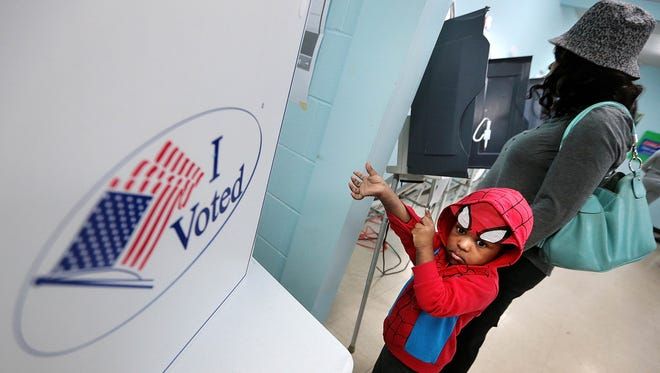 Yasim Blakely (2) waits for his mother Tina Obeid (right) as she casts her ballot at the Bellevue Frayser Baptist Church polling location Tuesday morning in Frayser.