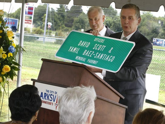 State Rep. Joe Pitts holds a highway sign officials