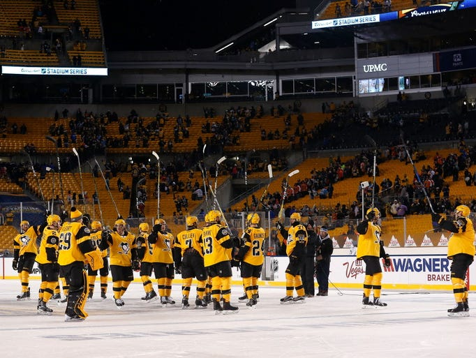 The Pittsburgh Penguins wave to their fans before leaving