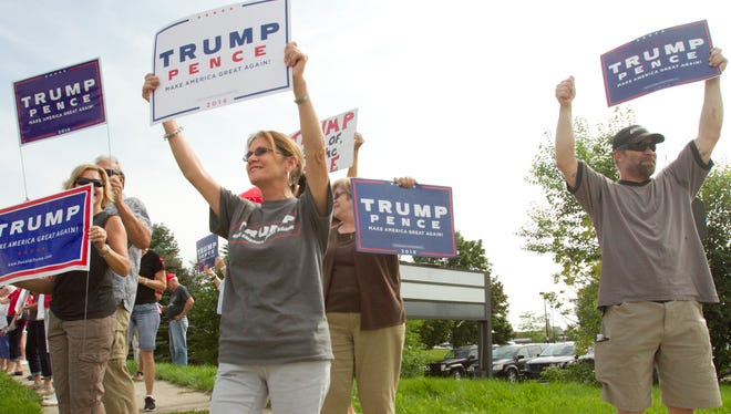 """Bonney Furman of Howell, in front center, Jesse Welker of Brighton, at right, and other Trump supporters gathered in a """"flash mob"""" gathering at the intersection of Charles Orndorf Drive and Grand River in Brighton, chanting for their candidate and receiving honks of support from drivers passing by Tuesday afternoon."""