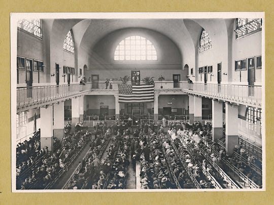Immigrants seated in the Great Hall of the U.S. Immigration