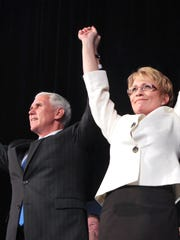 Victorious in their big to become Indiana's next Governor and Lt. Governor, Congressman Mike Pence and Rep. Sue Ellspermann, R-Ferdinand hold up their hands on stage at Lucas Oil Stadium in Indianapolis where Indiana Republicans gathered on election night, Tuesday, Nov. 6, 2012. Charlie Nye / The Star.