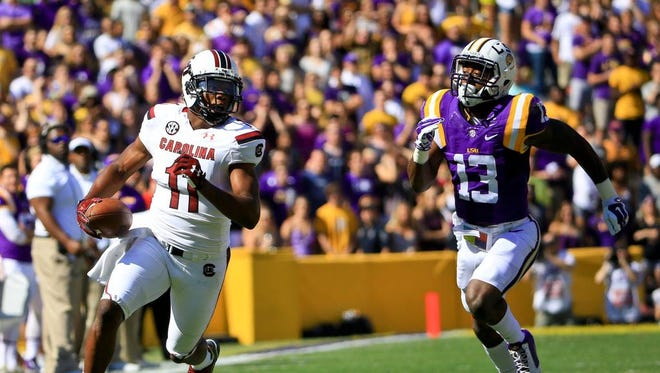 Oct 10, 2015; Baton Rouge, LA, USA; South Carolina Gamecocks wide receiver Pharoh Cooper (11) runs after a catch as LSU Tigers defensive back Dwayne Thomas (13) pursues during the first quarter of a game at Tiger Stadium.  Mandatory Credit: Derick E. Hingle-USA TODAY Sports