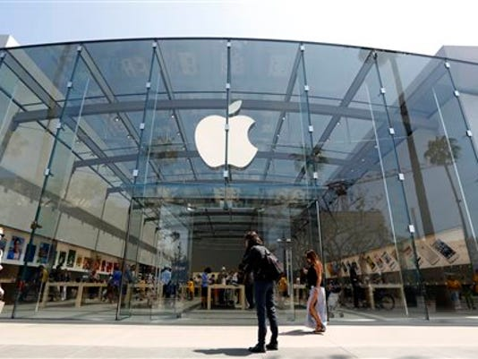 FILE - In this Thursday, May 9, 2013 file photo, people walk near the Apple store in Santa Monica, Calif.