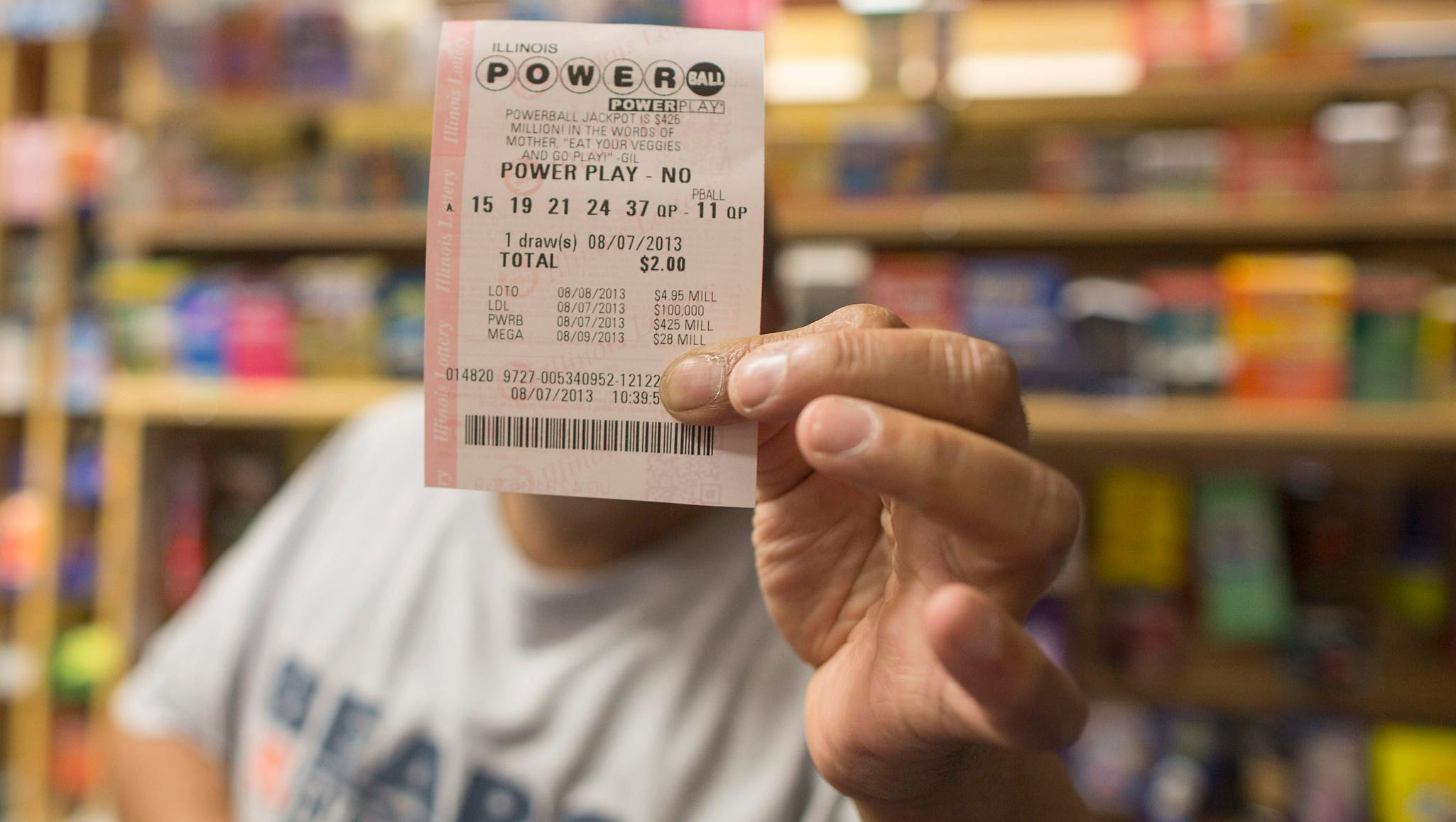 A man holds up his Powerball lottery ticket at a convenience store on Aug. 7 in Chicago. The lump-sum payout, after taxes, for the estimated $425 million jackpot is $244.7 million.