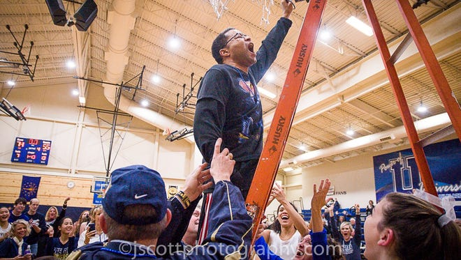 University High superfan Dr. Chris Cosby snips a bit of net after the team won its sectional championship.