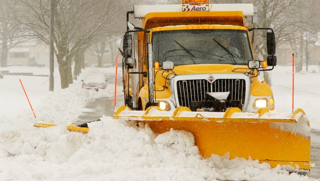 A snowplow clears the street during a past winter storm in Manitowoc.