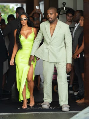 Kim Kardashian shined extra bright in neon as she and Kanye West arrive at Miami's Versace Mansion for rapper 2Chainz's wedding. The fashion diva wore a fluorescent green gown for the extravagant ceremony, and her husband bared his chest in a light-colored suit.