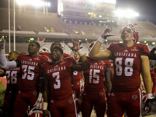 UL football players stand after a 2015-ending loss